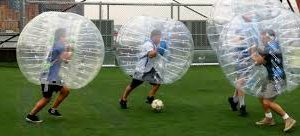 Boys playing soccer inside of battle ball inflatables.